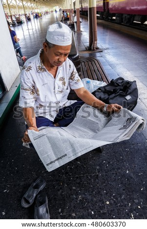 Bangkok, Thailand - September 4, 2016 : The old muslim man at platform, read newspaper while wait for  departure time at the head terminal train station in Bangkok.