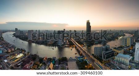 Bangkok Transportation at Dusk with Modern Business Building along the Chao Phraya river (Thailand) - stock photo