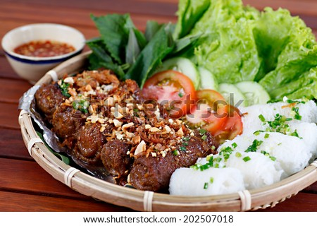 BANH HOI THIT NUONG - Typical Vietnamese cuisine: Pork grilled and extremely thin flat  rice vermicelli  in roll shape. - stock photo