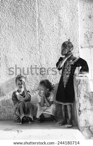 BANJUL, GAMBIA - MAR 14, 2013: Three unidentified Gambian girls play in the street in Gambia, Mar 14, 2013. Major ethnic group in Gambia is the Mandinka - 42% - stock photo