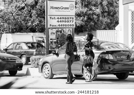 BANJUL, GAMBIA - MAR 14, 2013: Unidentified Gambian girls crossing the street and talking in Gambia, Mar 14, 2013. Major ethnic group in Gambia is the Mandinka - 42% - stock photo