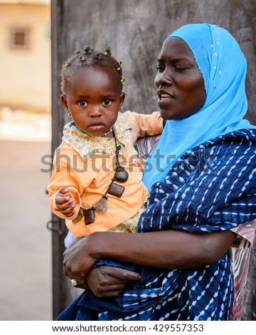 BANJUL, GAMBIA - MAR 14, 2013: Unidentified Gambian lady holds her little daughter on her hands in Gambia, Mar 14, 2013. Major ethnic group in Gambia is the Mandinka - 42%
