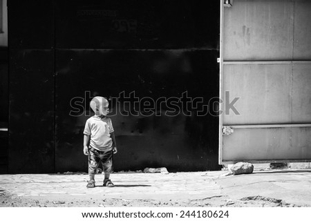 BANJUL, GAMBIA - MAR 14, 2013: Unidentified Gambian little boy stays in the street in Gambia, Mar 14, 2013. Major ethnic group in Gambia is the Mandinka - 42% - stock photo