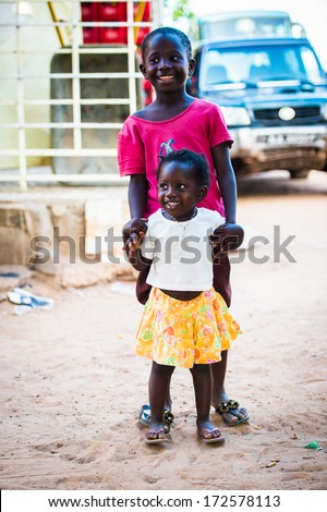 BANJUL, GAMBIA - MAR 14, 2013: Unidentified Gambian little girl in a shirt and yellow skirt poses in the street in Gambia, Mar 14, 2013. Major ethnic group in Gambia is the Mandinka - 42%