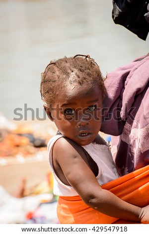 BANJUL, GAMBIA - MAR 14, 2013: Unidentified Gambian little girl is carried on her mother back in Gambia, Mar 14, 2013. Major ethnic group in Gambia is the Mandinka - 42%
