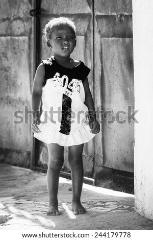 BANJUL, GAMBIA - MAR 14, 2013: Unidentified Gambian little smiling girl in Gambia, Mar 14, 2013. Major ethnic group in Gambia is the Mandinka - 42% - stock photo