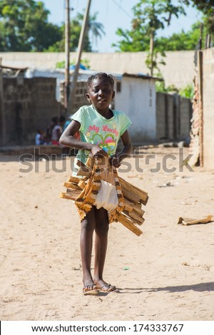 BANJUL, GAMBIA - MAR 14, 2013: Unidentified Gambian little smiling girl plays with a banch of wood in the street in Gambia, Mar 14, 2013. Major ethnic group in Gambia is the Mandinka - 42%
