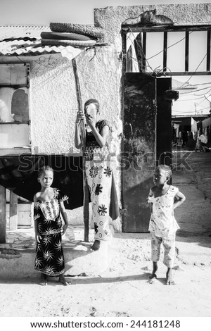 BANJUL, GAMBIA - MAR 14, 2013: Unidentified Gambian mother and her children walk in the street in Gambia, Mar 14, 2013. Major ethnic group in Gambia is the Mandinka - 42% - stock photo