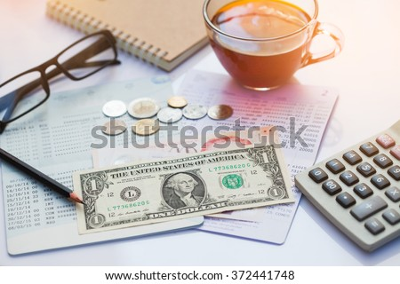 Bank account, Pencil, dollar, cions  and calculator with a cup of tea. - stock photo