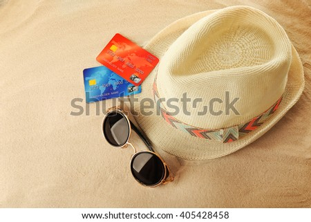 Bank card with male hat and sunglasses on sand background - stock photo