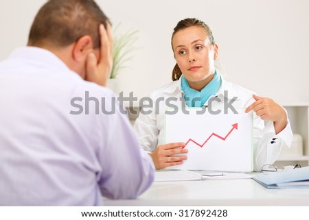 Bank clerk shows her depressed client that the mortgage has gone up. - stock photo