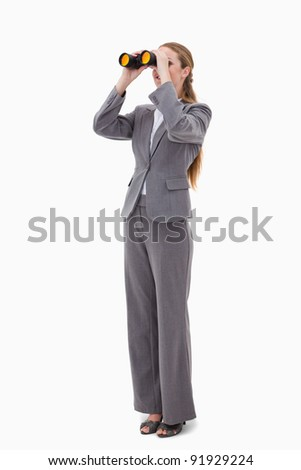 Bank employee looking through binoculars against a white background - stock photo