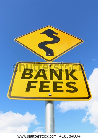 bank fees going up on a yellow and black road sign in a blue sky - stock photo