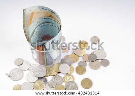 Bank notes in the glass and coins  isolated on wooden table. Business concept. DOF and copy space.