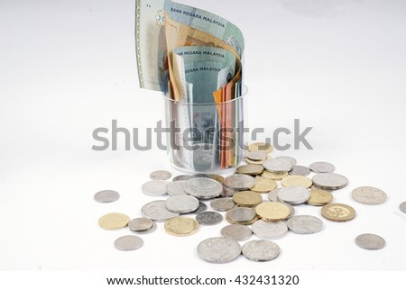Bank notes in the glass and coins  isolated on wooden table. Business concept. DOF and copy space.  - stock photo