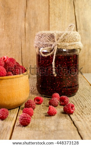 Bank of raspberry jam and fresh raspberries