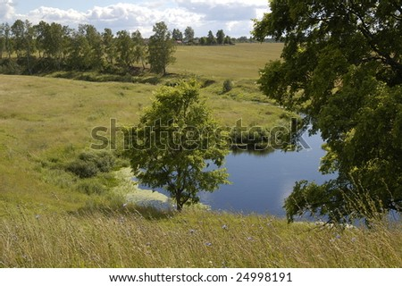 bank of the river near the village - stock photo