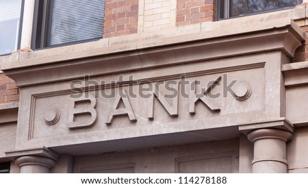 Bank Sign Carved in Stone on Building in Historic Downtown - stock photo