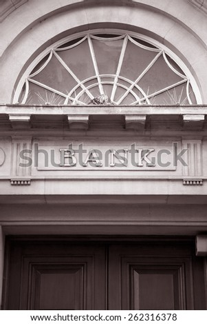 Bank Sign over Entrance Door in Black and White Sepia Tone - stock photo