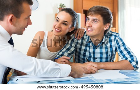 Banking agent offering positive young couple good conditions of mortgage indoors
