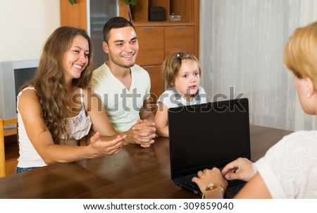 Banking assistant and satisfied family arranging mortgage details. Focus on woman - stock photo