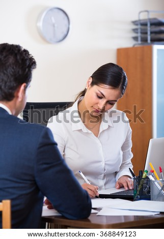 Banking positive agent listening to customer and smiling in agency