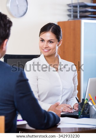Banking positive russian agent listening to customer and smiling in agency - stock photo