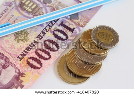 Banknote and coins (Hungarian currency) with a pen