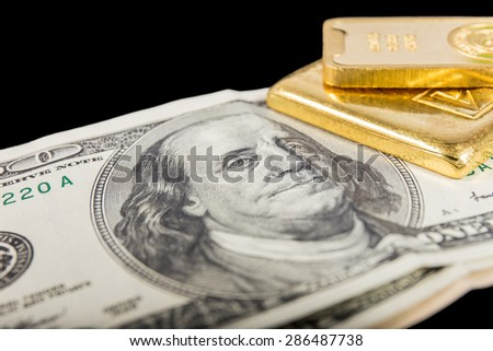banknote and gold bullion isolated on black - stock photo