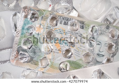 Banknote 50 Bahamian cent on an empty blister pack of tablets - stock photo
