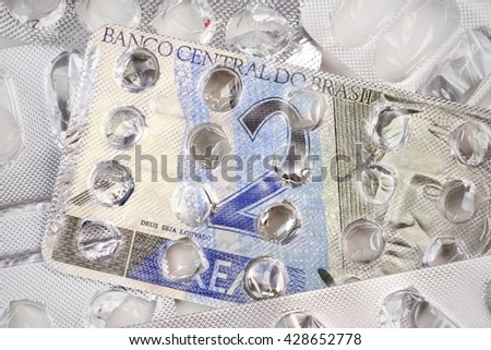 Banknote 2 Brazilian reals on an empty blister pack of tablets - stock photo