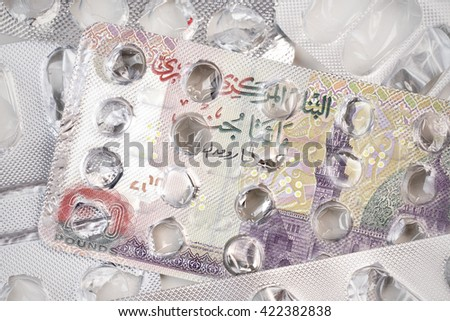 Banknote 200 Egyptian pounds on an empty blister pack of tablets - stock photo
