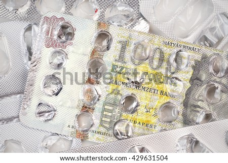 Banknote 1000 Hungarian forints on an empty blister pack of tablets - stock photo