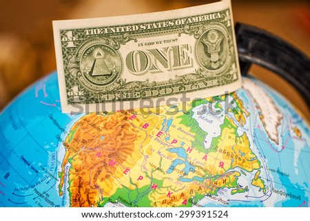 Banknote one dollar is worth on the globe from above. - stock photo