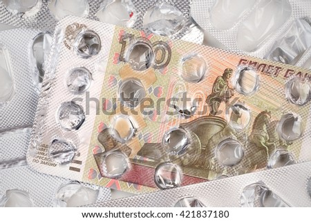 Banknote 100 Russian rubles on an empty blister pack of tablets - stock photo