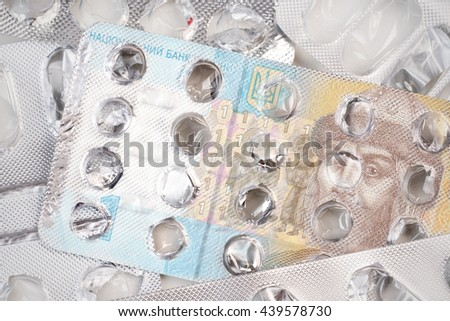 Banknote 1 Ukrainian hryvnia on an empty blister pack of tablets - stock photo