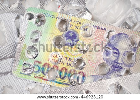 Banknote 50000 Vietnamese Dong on an empty blister pack of tablets - stock photo