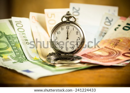 banknotes and a pocket watch on a wooden table