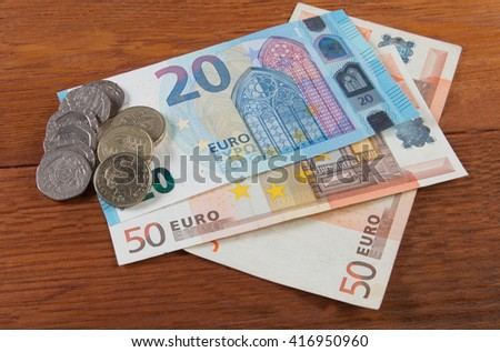 Banknotes and coins on the table - stock photo