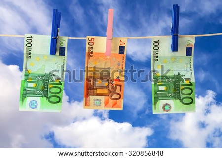 Banknotes Euro hanging on clothesline on blue sky background - stock photo