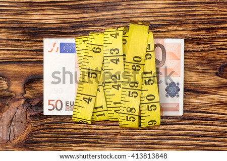 Banknotes 50 euros tied with measuring tape - stock photo