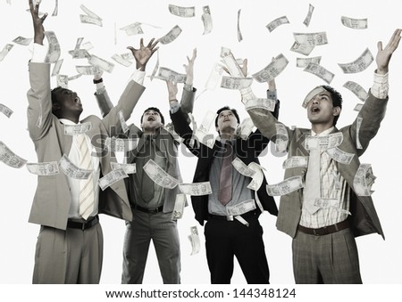Banknotes falling over four businessmen - stock photo