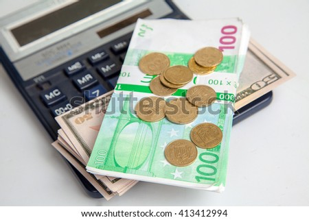 banknotes lie on a calculator. dollars, euros and coins. concept of financial crisis and savings
