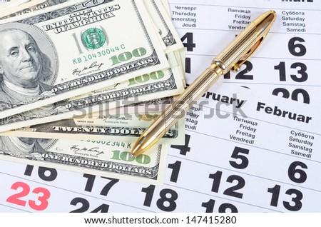 Banknotes of dollars on calendar sheets close-up - stock photo