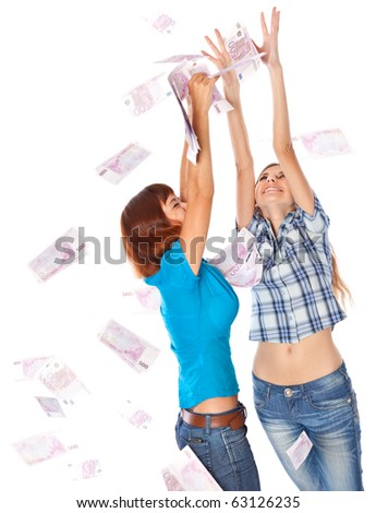 Banknotes of 500 euro are falling on two girls. Isolated on white background