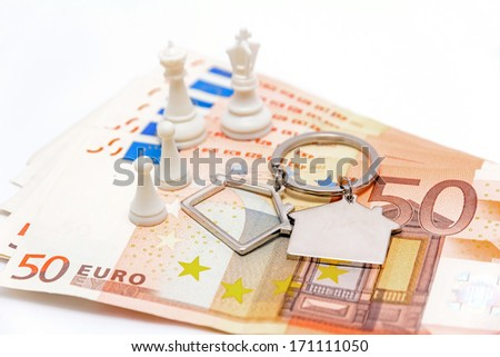 Banknotes of fifty euro isolated on white background with house-shaped key-chain and chess pawns posing as family, concept for houses on loans  - stock photo