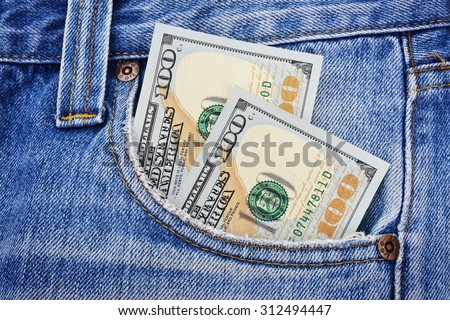 Banknotes of one hundred american dollars in the jeans pocket