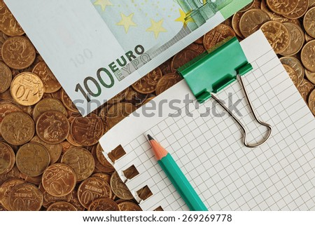 Banknotes of one hundred euros and blank page on coins - stock photo