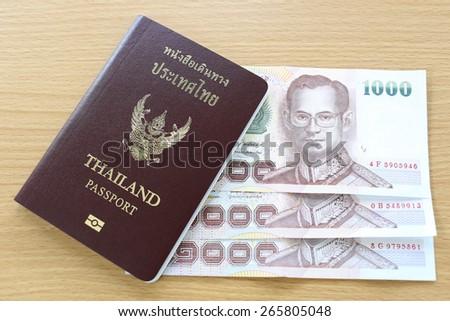 Banknotes of Thailand in thai passport. - stock photo