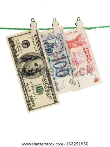 banknotes USA, Russia and Moldova are fixed on a green rope with clothespins.